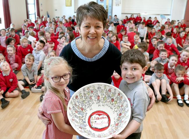 Ingrid Logan, principal of Lisbellaw Primary School being presented by a bowl with all the childrens figures and names on it from pupils Sophie Williams and Tom Brady.