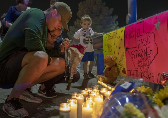 Rene Aguilar and Jackie Flores pray at a makeshift memorial for the victims of last Saturday's mass shooting at a shopping complex in El Paso, Texas, Sunday, Aug. 4, 2019. (AP Photo/Andres Leighton).