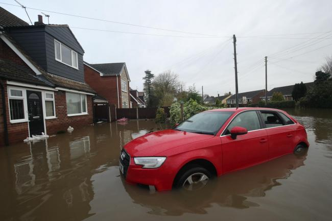 A car in floodwater outside a house in Fishlake
