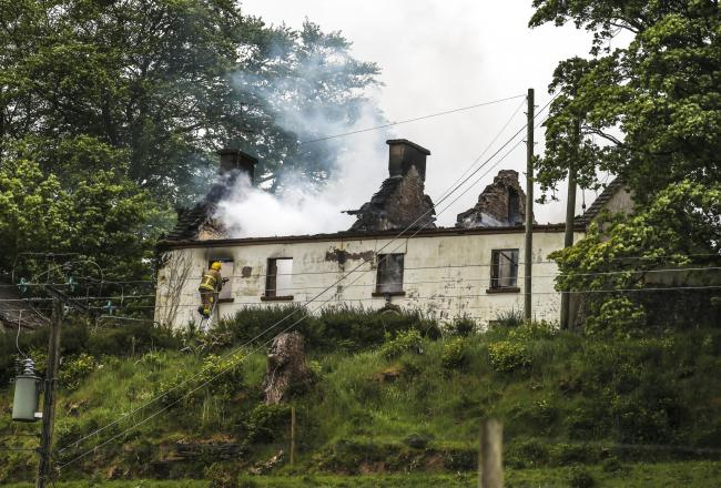 A firefighter tackles the blaze of a house fire near Pubble, Tempo..