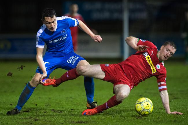 James McKenna battles for possession against Cliftonville's Chris Curran in 2018.