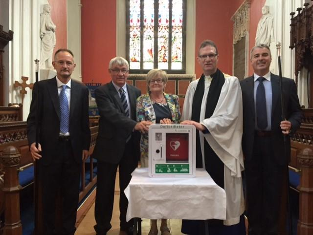 George and Myrtle Irvine making the presentation of a defibrillator to Dean Kenny Hall (centre) with Churchwardens Noel Johnston (left) and Raymond Campbell (right).