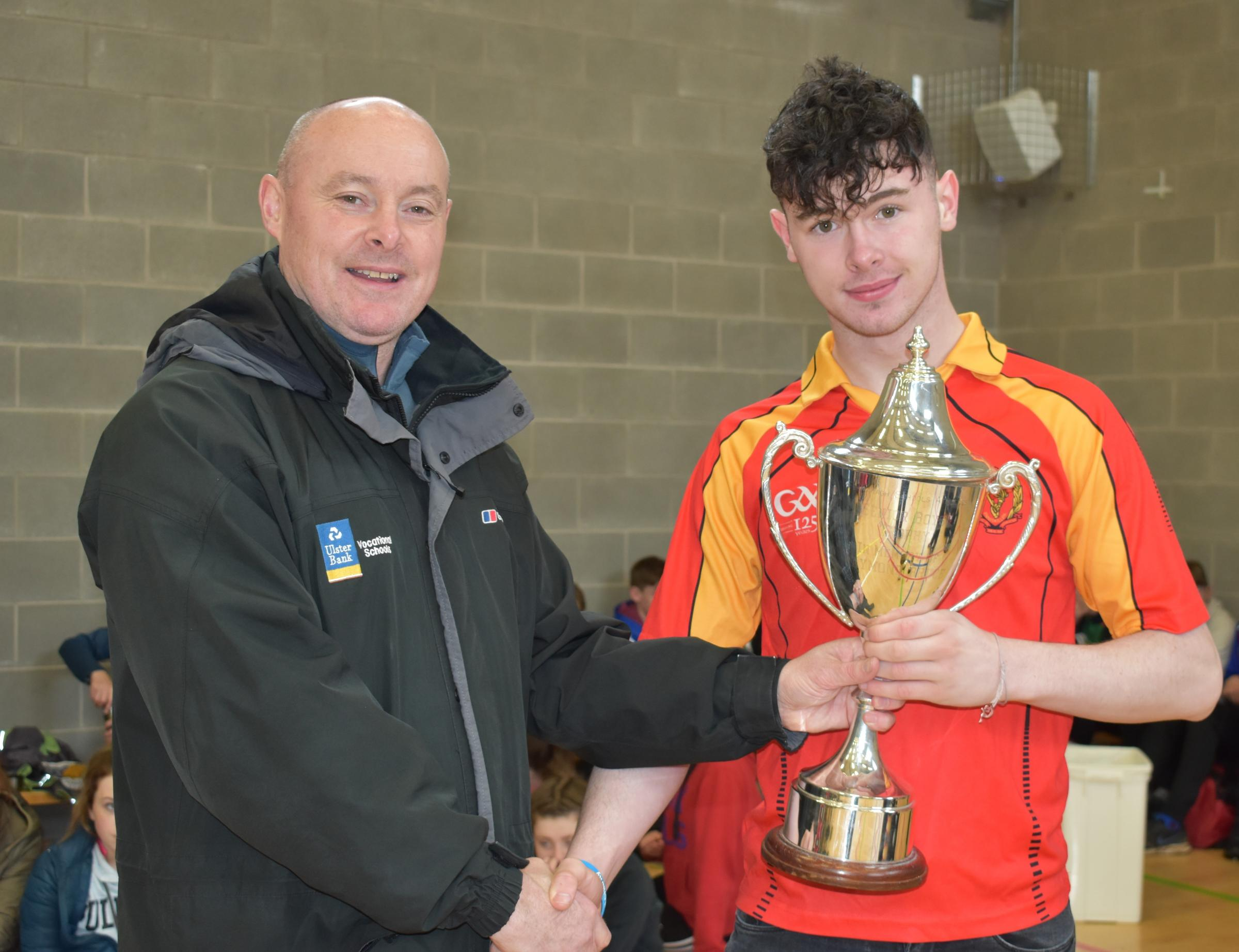 Malachy O'Rourke, St. Jospeh's College, presenting a cup to Ethan Rooney, winner of the 100m and 200m at captain of the successful St. Joseph's Senior Boys team.