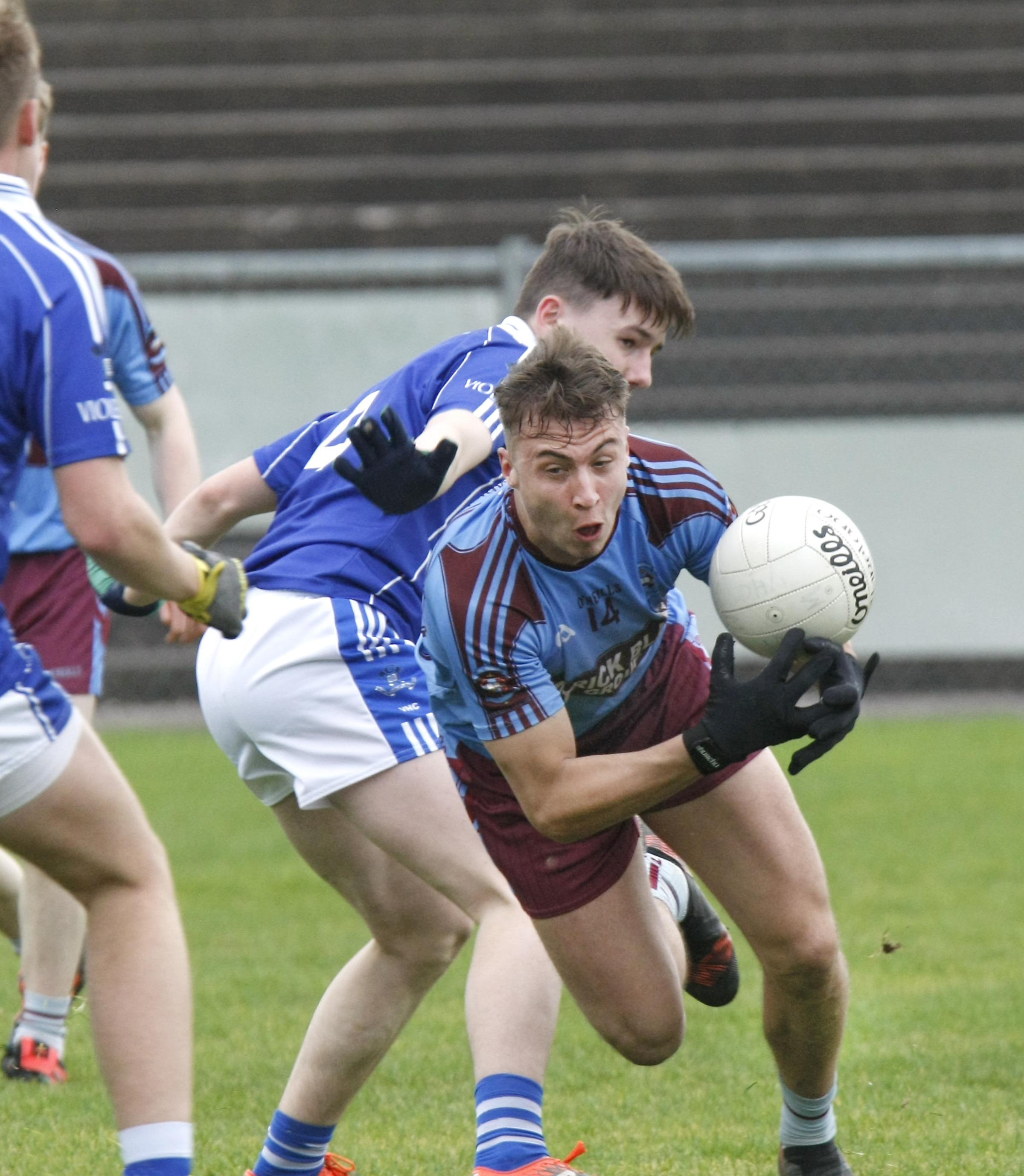 St Michael's Pol McKervey in a tussle for the loose ball with St Colman's Callum Billham