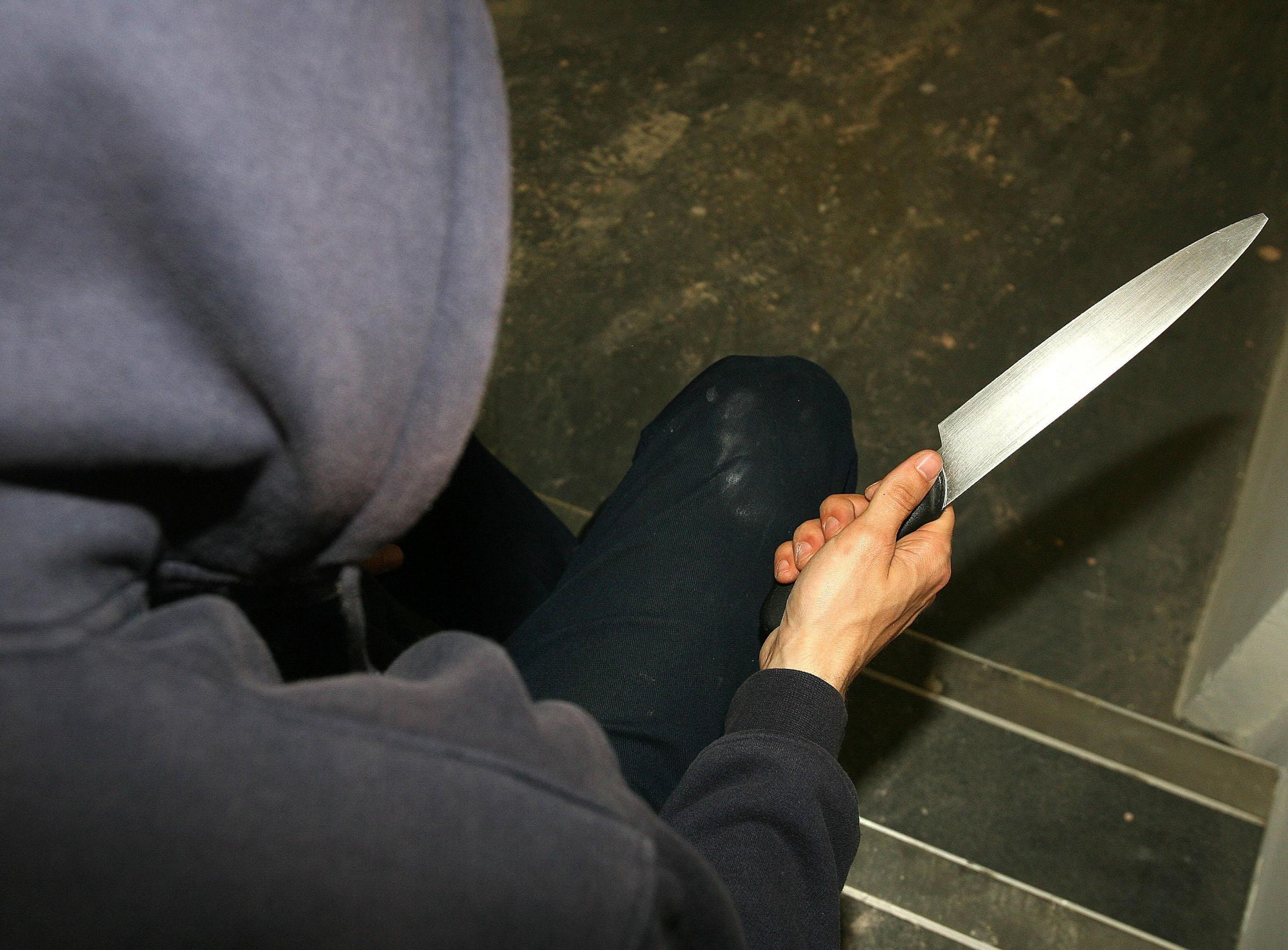 PICTURE POSED BY MODEL .File photo dated 25/4/09 of a man holding a knife. The Home Office is seeking new technology to help tackle surging levels of knife crime and initial funding of up to £500,000 is available for research projects that co